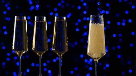 Filling a glass with sparkling wine in the dark