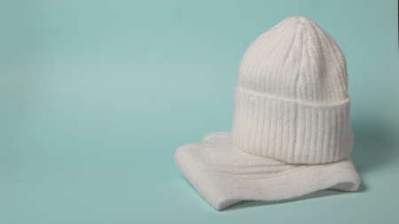 White knitted women's gloves and hat on a blue background. Fashionable winter accessories.
