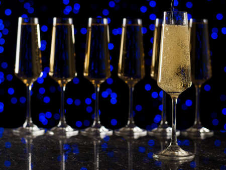 Sparkling wine is poured into a glass against a row of full glasses. Stock fotó - 159521832