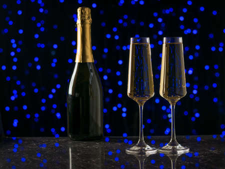Two filled glasses and a bottle of sparkling wine against blue bokeh Stock fotó - 159521831