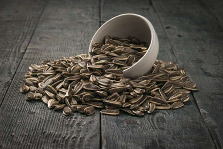 Large sunflower seeds are poured out of a ceramic bowl on a wooden table. The fresh yield of sunflower. Stock fotó - 159505581
