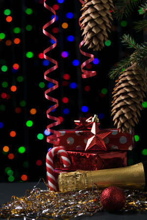 A closed bottle of champagne and Packed gifts under a Christmas tree. Meeting of Christmas and new year. Space for text.
