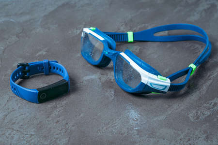 Smart bracelet and glasses for swimming on a stone background in water drops. Accessories for swimming in the pool. Stock fotó - 159576562