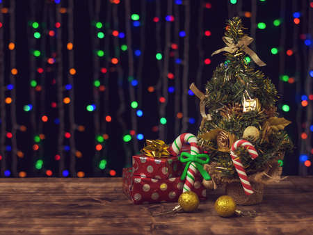 Christmas candies and gifts under a decorated spruce tree on a bokeh background. Christmas and New year celebrations. Space for text.