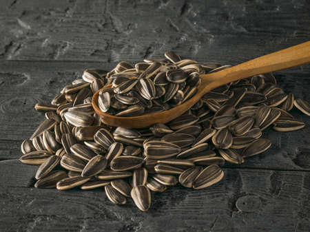 Wooden spoon in a pile of sunflower seeds on a dark wooden background. The fresh yield of sunflower.