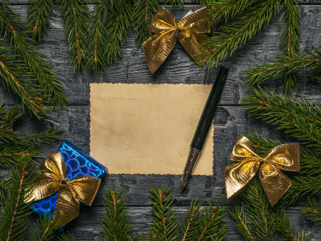 Gift, bows, pen and a sheet of antique paper on the background of fir branches. A letter requesting a gift.