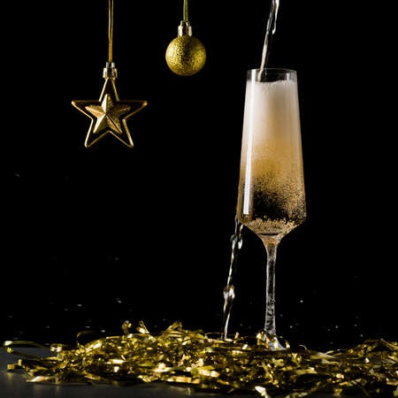 Sparkling wine spills past the glass and splashes on the table. A popular alcoholic drink.