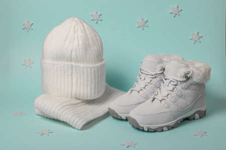 Knitted hat and scarf and white winter sneakers on a blue background with snowflakes. Fashionable winter accessories.