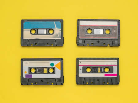 Four tape recorders on a yellow background. Retro carrier of audio information.