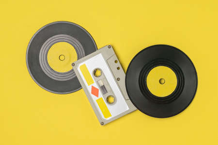 Audio cassette with magnetic tape and vinyl discs on a yellow background. Retro devices for storing and playing audio recordings.