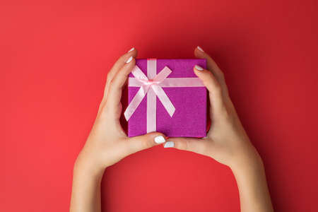Women's hands with a gift box with a bow on a red background. Surprise in the hands of a girl.