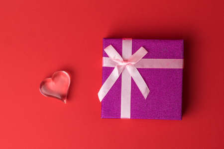 Gift box with bow and glass heart on red background. A Declaration of love. Zdjęcie Seryjne