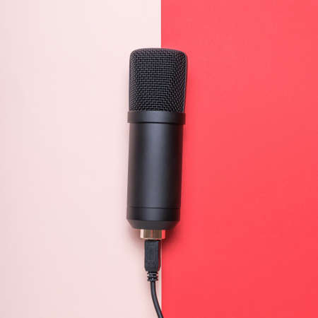Microphone with connected wire on red and pink background. Sound recording equipment.