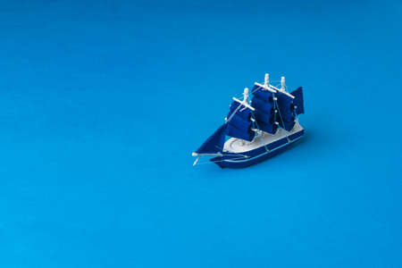 A toy wooden sailboat on a dark blue background imitating the sea. The concept of travel and adventure.