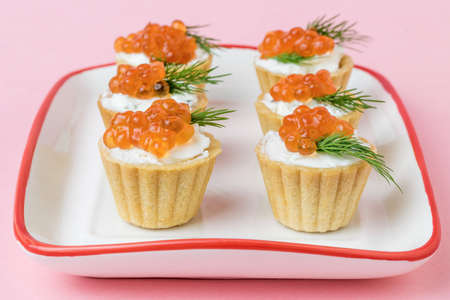 White and red bowl with tartlets on a pink background. Appetizer with sea delicacies.