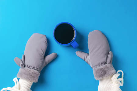 A girl's hands in mittens and a cup of black coffee on a blue background. Hot drink and mittens.