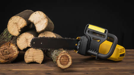 Chain saw with sawn wood parts on a wooden background. Electric tool for wood processing.