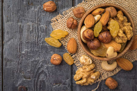 A mixture of dried fruits and nuts in a wooden bowl on a piece of burlap on a wooden table. Natural healthy vegetarian food. Flat lay. Imagens