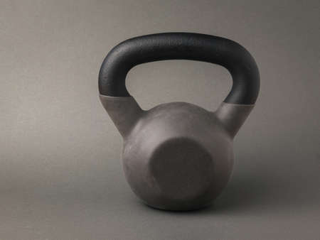 A gray sports kettlebell on a dark gray background. Sports lifestyle.