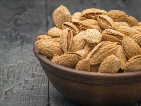 An earthenware bowl with unpeeled almonds on a black wooden table. Vegetarian food. Stock fotó