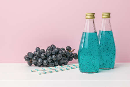 Dark blue grapes and two bottles of a cocktail with basil seeds on a pink background. An exotic drink.