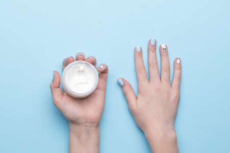 A jar of cream in women's hands with a stylish manicure on a blue background. Hand skin care. Flat lay. Stock fotó
