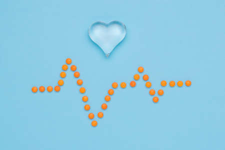 A drawing of a cardiogram made of orange pills and a glass heart on a blue background. The concept of treatment of heart diseases.