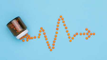 Orange pills are poured out of the bottle in the form of a cardiogram. The concept of treatment of heart diseases.