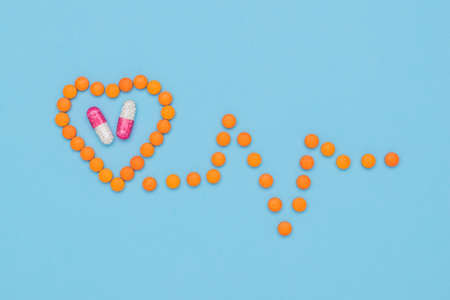 Heart and cardiogram made from orange pills. The concept of treatment of heart diseases. Stock fotó