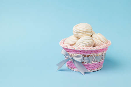 Pink wicker basket with homemade meringue on a pink background. Delicious sweetness of eggs and sugar.
