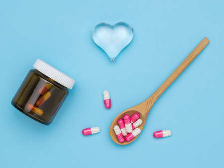 A wooden spoon and a bottle of medicinal capsules and a glass heart. The concept of treatment of heart diseases. Stock fotó