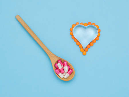 A spoon with medicinal capsules and a glass heart with pills on a blue background. The concept of treatment of heart diseases. Stock fotó