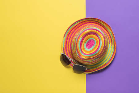 Top view of a colorful summer hat with glasses on a yellow and purple background. Summer headdress. Stock fotó
