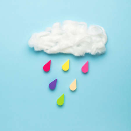 A cloud and six multicolored drops on a light blue background. Collage of modern art. Climate picture.