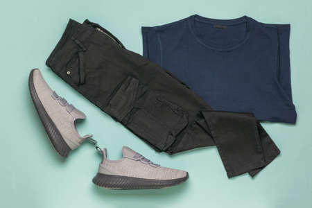 A pair of gray sneakers, black pants, and a pullover on a blue background. Fashionable youth casual clothing.