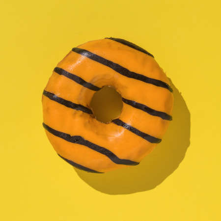 Orange donut in bright light on yellow background. Delicious popular pastries.