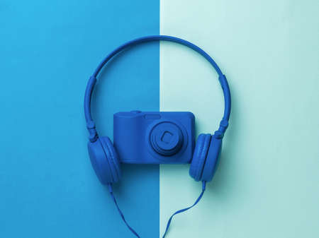 Headphones and camera are bright blue on a two-tone background. Stylish equipment for photo and video shooting.