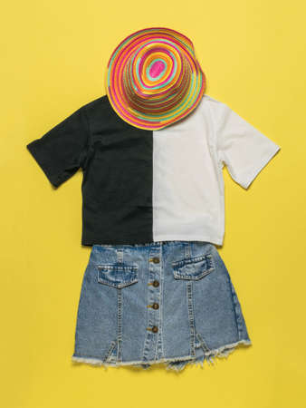 Summer hat, T-shirt and denim skirt on a yellow background. A set of summer clothes. Stock fotó