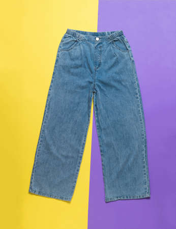 Fashionable wide summer women's jeans on a two-tone background. Denim pants.
