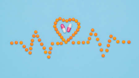 A cardiogram of pills and a heart with capsules on a blue background. The concept of treatment of heart diseases.