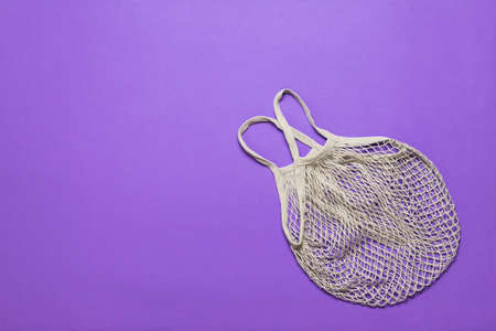 A gray mesh bag on a purple background. Vintage grocery bag.