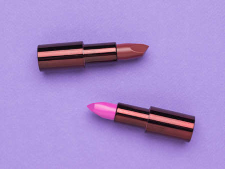 Two open tubes of lipstick on a purple background. Lip decoration. Flat lay.