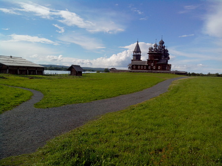 view of Kizhi Island, the historic site of churches and bell tower, a large historic log wood house on the marshy banks of island