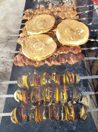 Juicy marinated in spices meat kebab on skewers, cooked and fried on a fire and charcoal barbecue grill, in the nature of snowy winter, on a clear day.