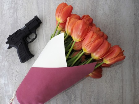 A bouquet of tulips and a black 9mm pistol on a gray background. The concept of the gift