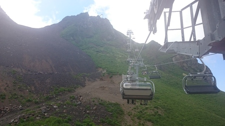 Mountain slope with cable cars and ski slopes on a cloudy summer day, fog, clouds. Black Pyramid Mountain, Krasnaya Polyana, Sochi, Caucasus, Russia