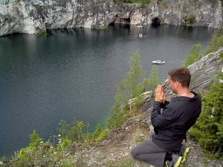 Man, back view praying on his knees. Russia. Karelia. Ruskeala mountain Park is a former marble quarry filled with groundwater