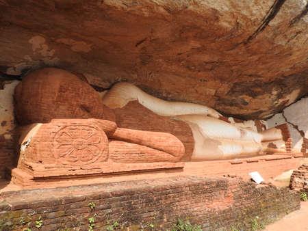 unfinished reclining Buddha statue located on Pidurangala rock, less famous rock formation in short distance of popular Sigiriya Lion Rock, Matale district, Sri Lanka, former Ceylon, South Asia.