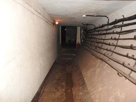 An abandoned prison in an underground bunker. A former Soviet cold war bomb shelter. The sealed door of the bunker. Pipes and valves. Low light condition. Bunker of fear and nightmares
