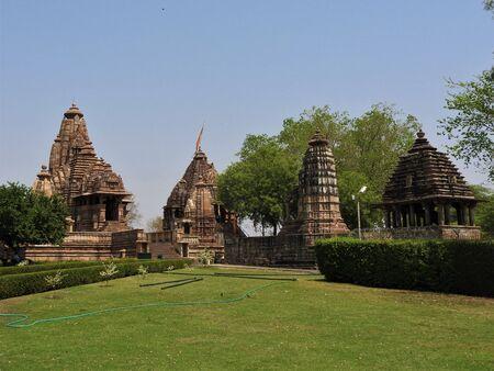 Beautiful image of Kandariya Mahadeva temple, Khajuraho, Madhyapradesh, India with blue sky and fluffy clouds in the background, world famous ancient temples in India Фото со стока